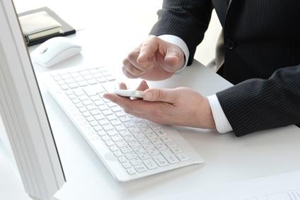 ידיו של הגבר עם הנייד ליד מקלדת המחשב
