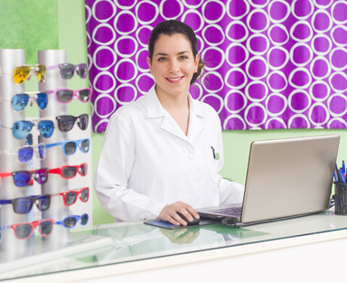 WOman in optical store with laptop and glasses stand