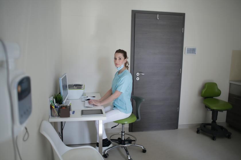 רופא המשתמש במחשב באמצעות תוכנה לניהול קליניקה